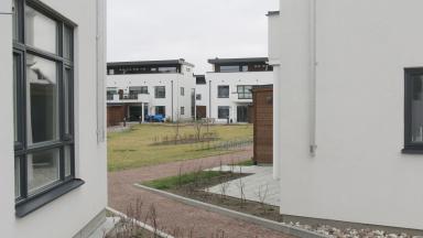 Hus med vit fasad och innegård